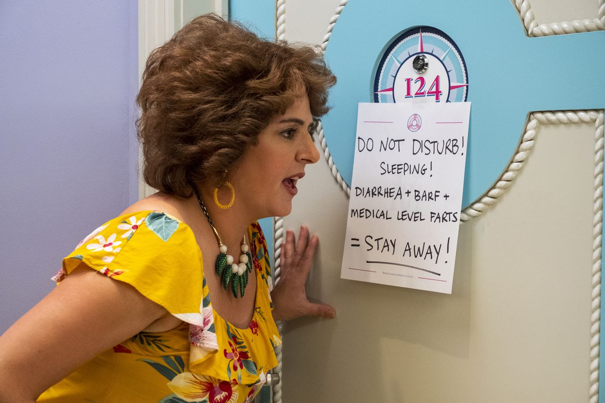 "Annie Mumolo as Barb looking at a sign that says ""Do Not Disturb! Sleeping! Diarrhea + Barf = Medical Level Farts!"""