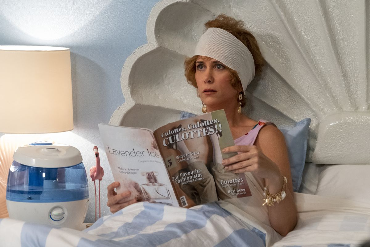 Kristin Wiig as Star reading a Culottes magazine in bed in Barn & Star