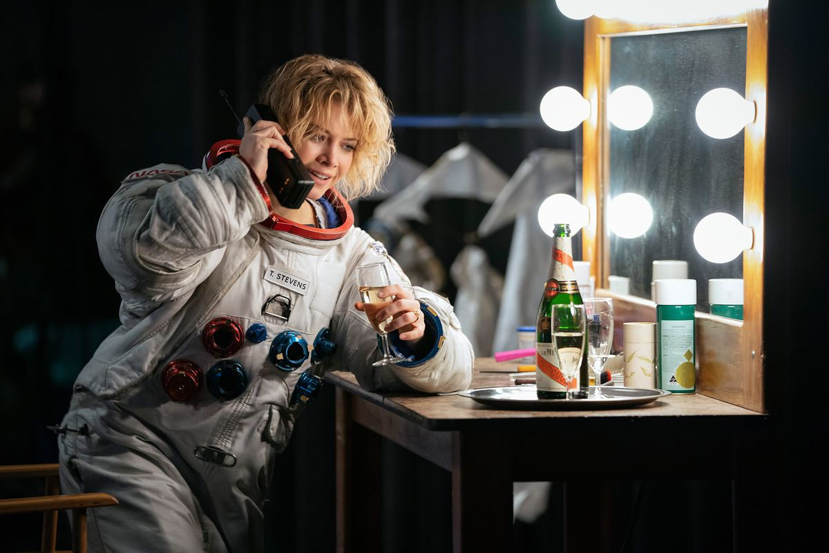 Sarah Jones in an astronaut flight suit talks on a giant mobile phone in front of a lighted makeup mirror in For All Mankind season 2