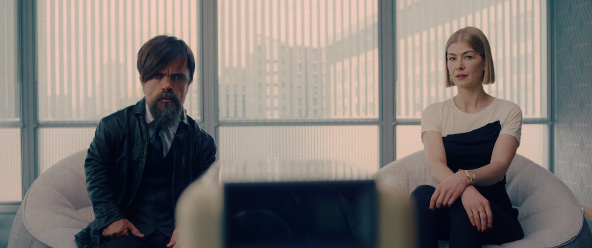 Peter Dinklage and Rosamund Pike sit in chairs in front of a bright window together, watching something on a foregrounded screen in I Care a Lot