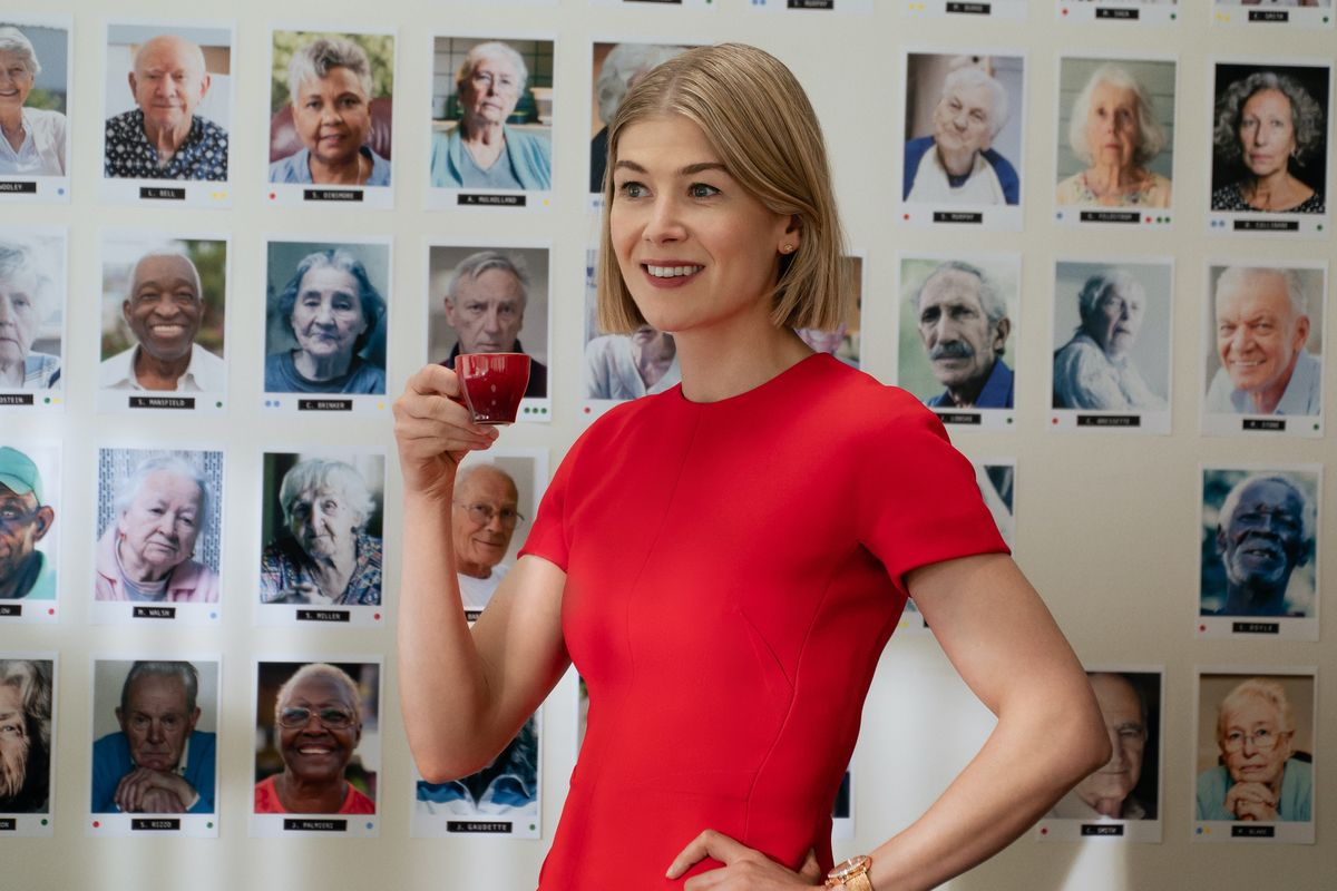 A smiling Rosamund Pike holds up a tiny red mug as she stands in front of a wall of photos of elderly people in I Care a Lot