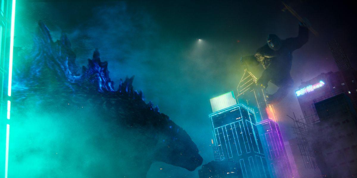 King Kong overlooks Godzilla atop a neon skyscraper at night in Godzilla vs. Kong