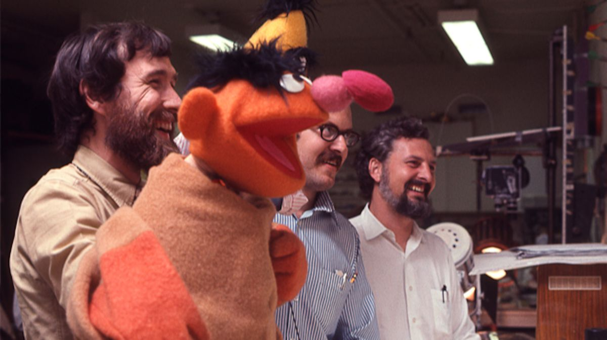 Puppeteers Jim Henson and Frank Oz and Sesame Street Jon Stone hold up an Ernie puppet in the behind-the-scenes documentary Street Gang