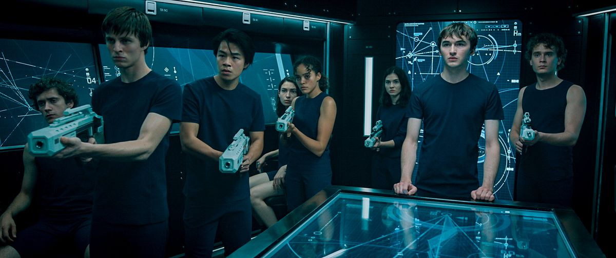 A group of rebellious space-teenagers in matching blue shirts, clutching futuristic plastic guns and standing in front of space-charts