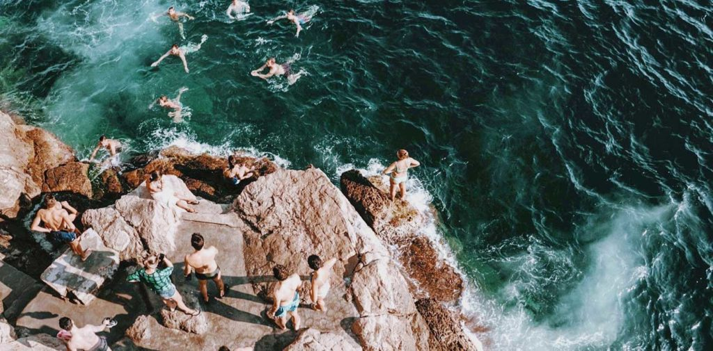 Group of young people jumping off cliff into water below