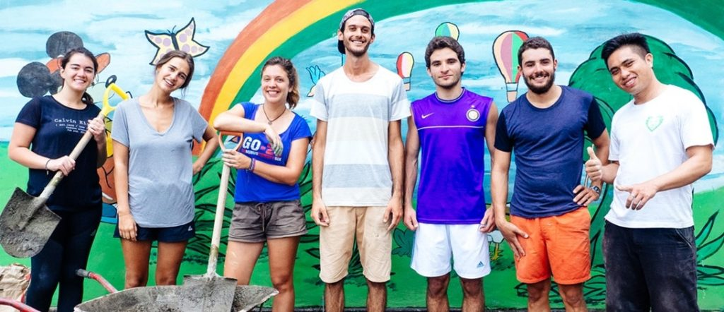 Group of young travelers holding shovels, posing in front of a colorful mural
