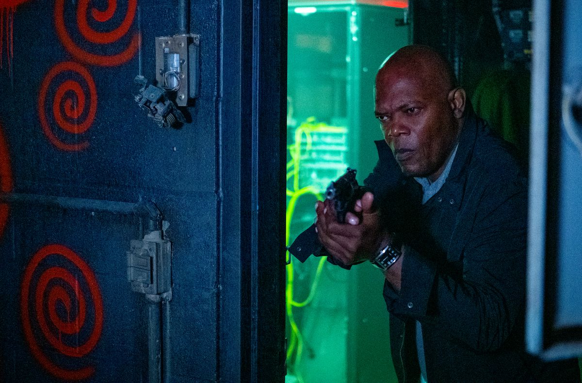 Samuel L. Jackson, gun drawn, looks into a room with red spray-painted spirals on the walls
