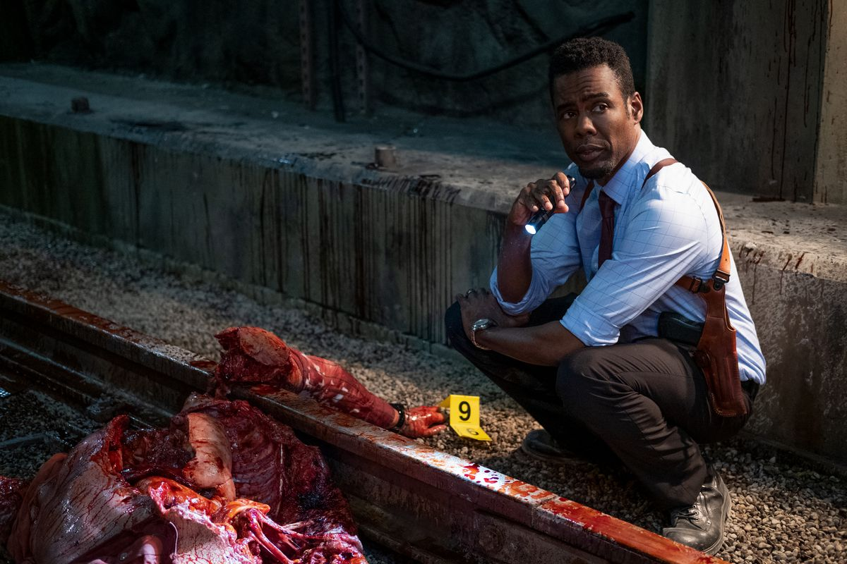 Chris Rock squats by a skinless, shredded human body on train tracks in Spiral: From the Book of Saw