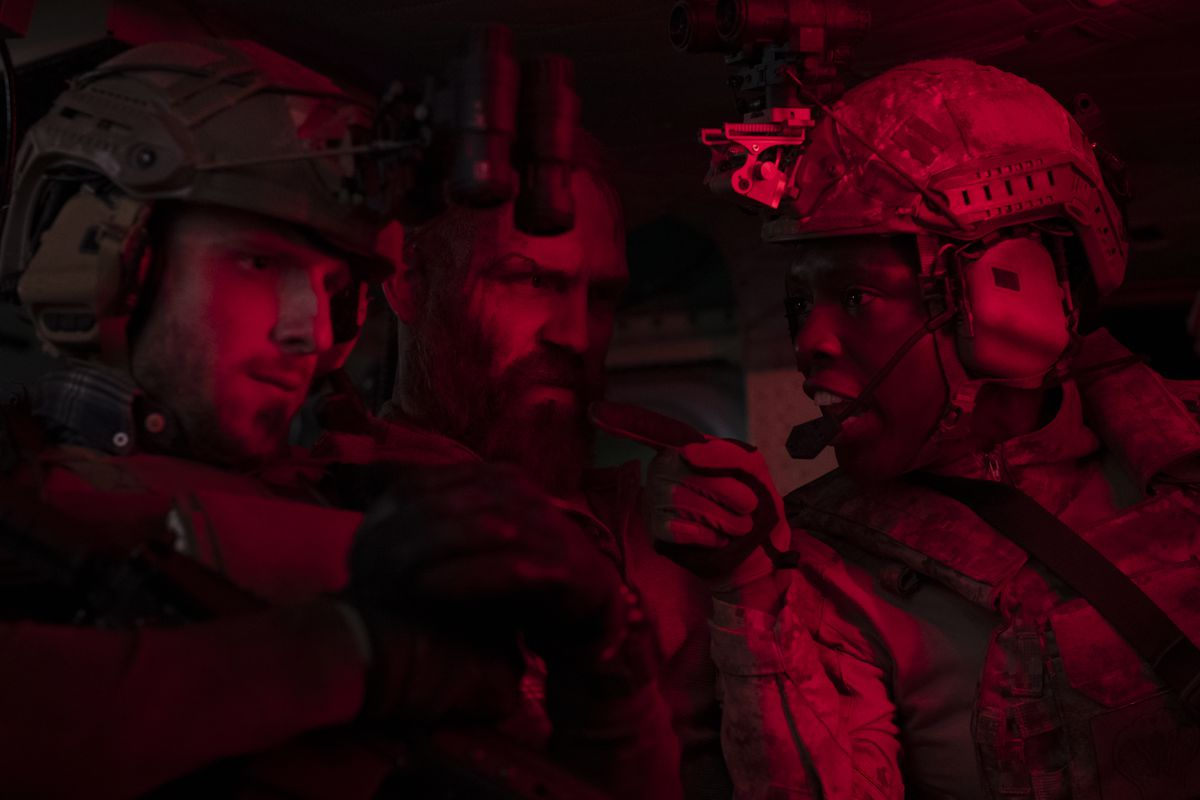 Jamie Bell, Jack Kesy, and Jodie Turner-Smith huddle in dim red light as Navy SEALs in Without Remorse