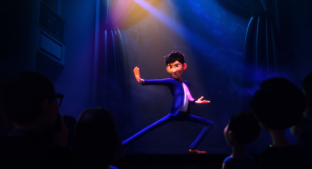 Din, in a blue suit and pink tie, poses in a dramatic kung-fu-style pose onstage in front of an audience in Wish Dragon