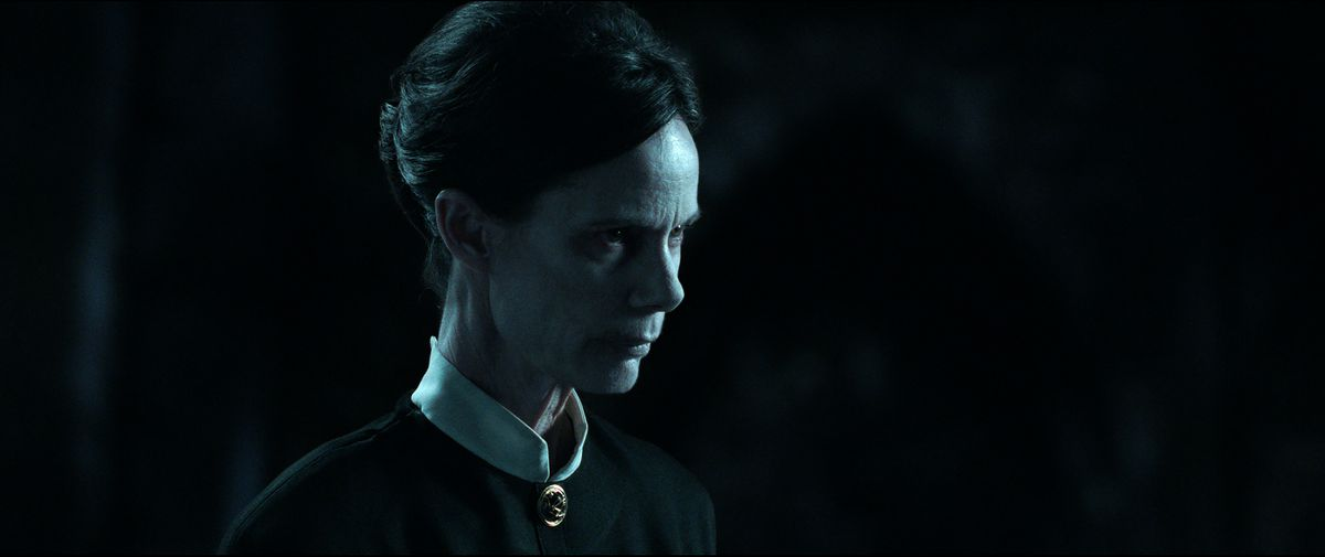 A severe looking person in muted blue light in The Conjuring: The Devil Made Me Do It