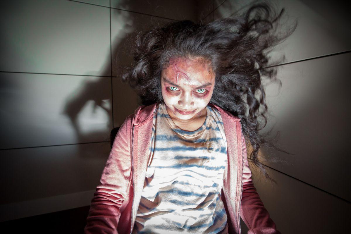 A demon girl (Erika Camacho) smiles menacingly at the camera as her hair blows back in Wellington Paranormal