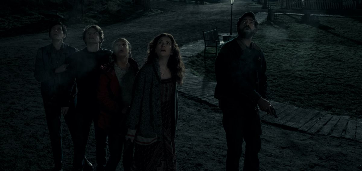 A group of people walking on a dark nighttime path gape upward together in Midnight Mass