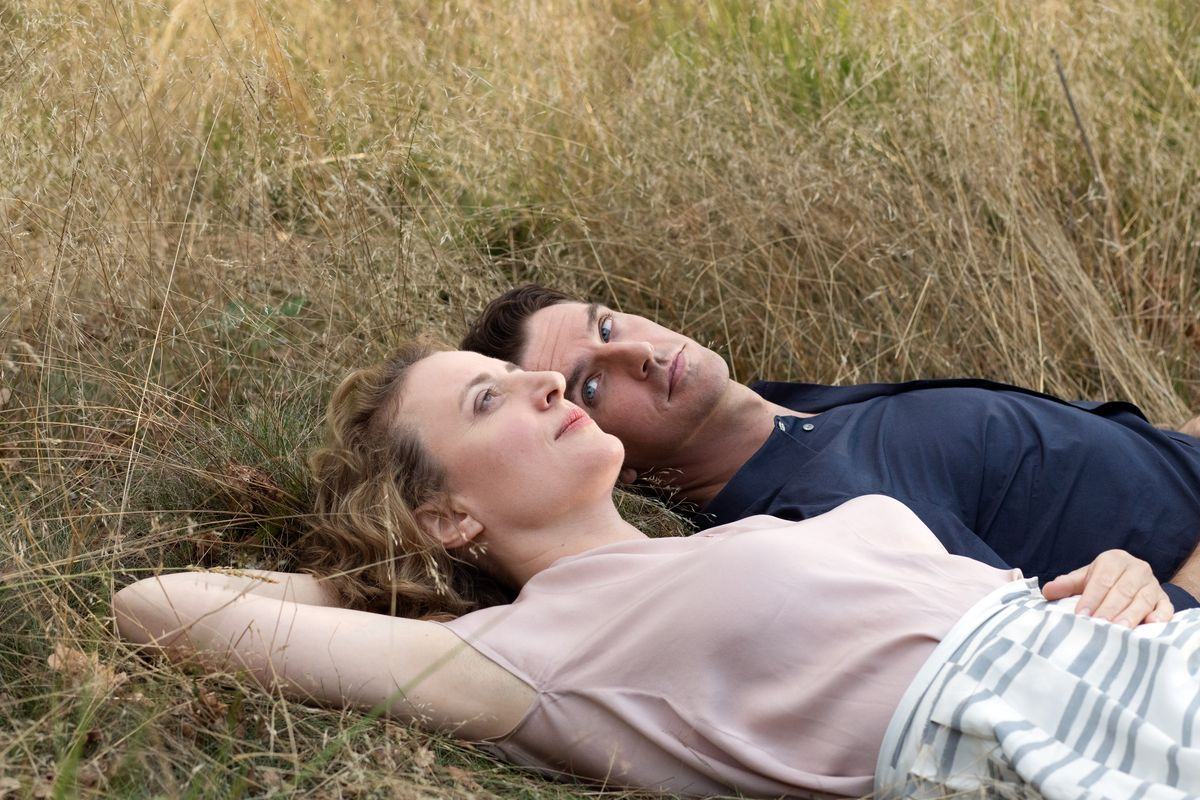 Maren Eggert and Dan Stevens lie in the grass together in I'm Your Man
