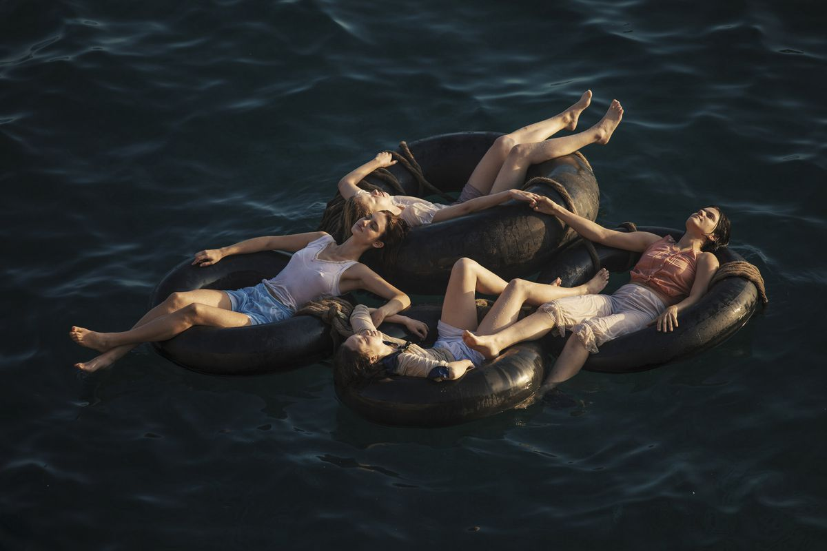 The women of Mayday lounge on floating inner tubes on the ocean, holding hands to stay together